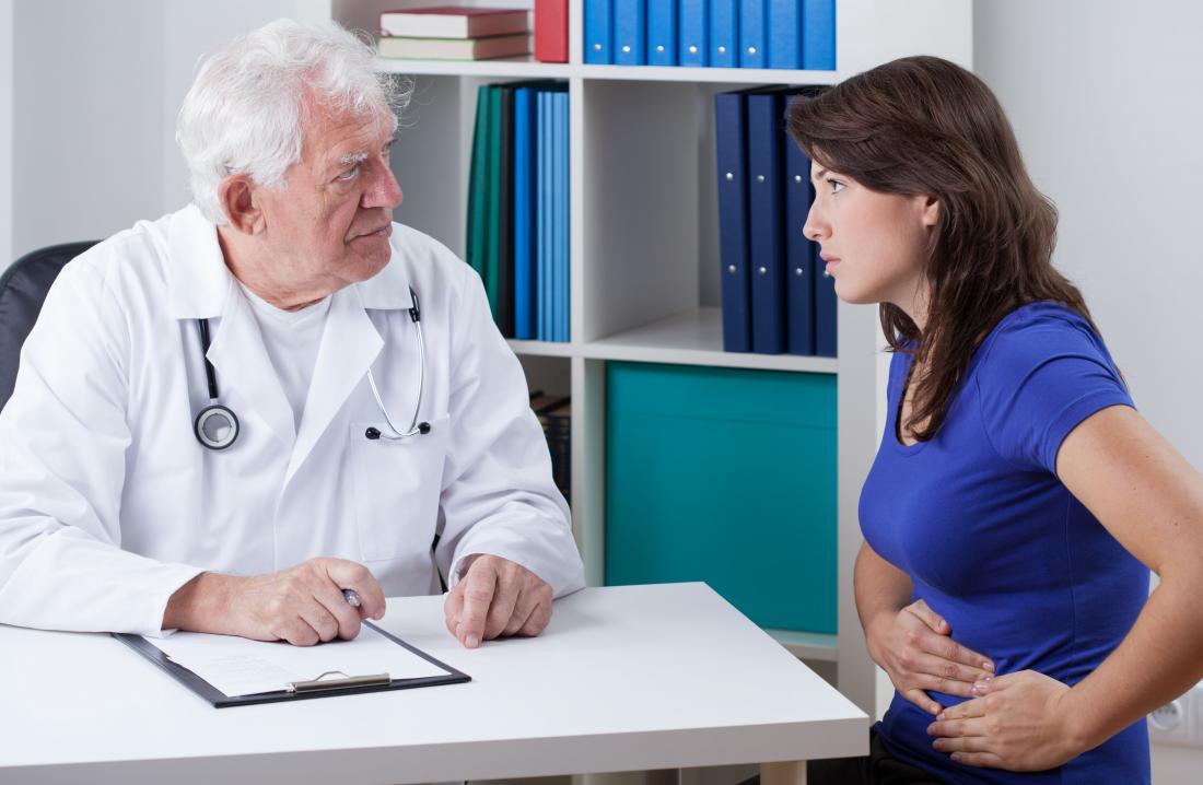 Donna con mal di stomaco addominale parlando al medico.