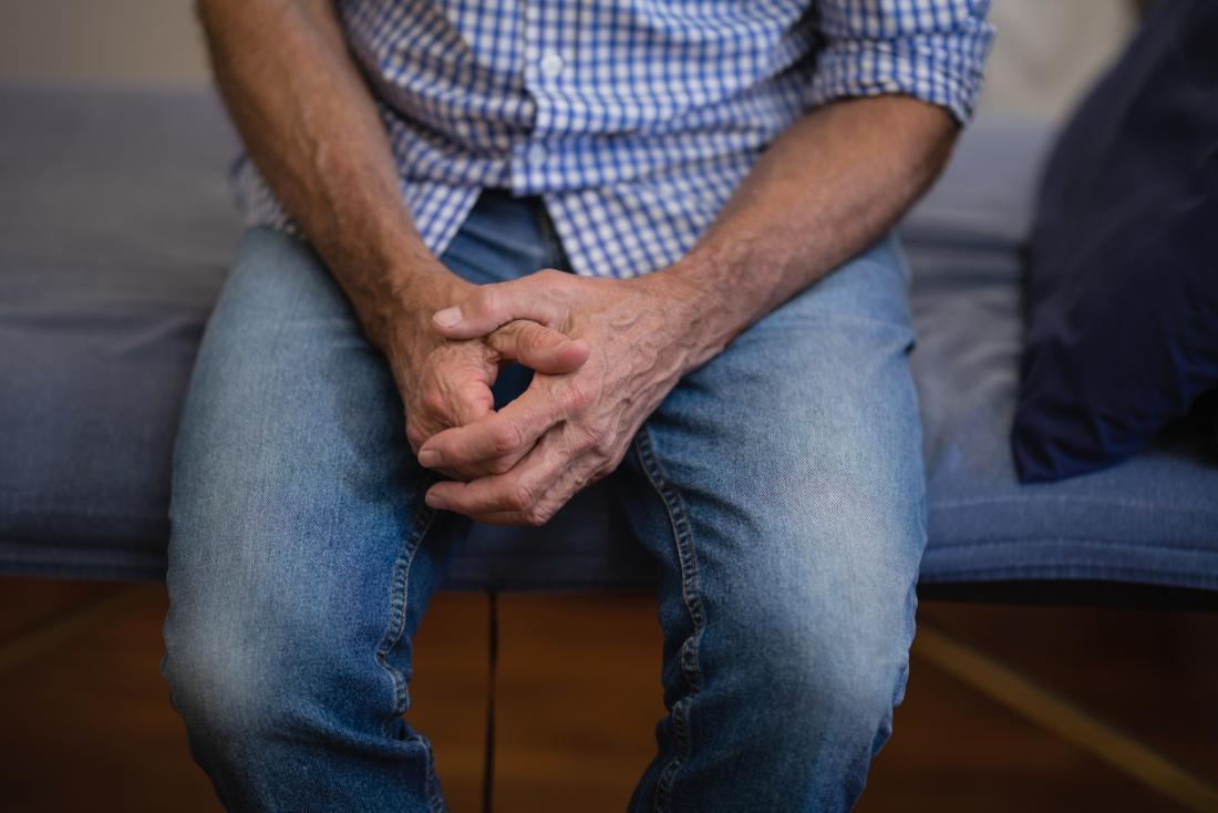 homme assis sur le lit avec les mains jointes