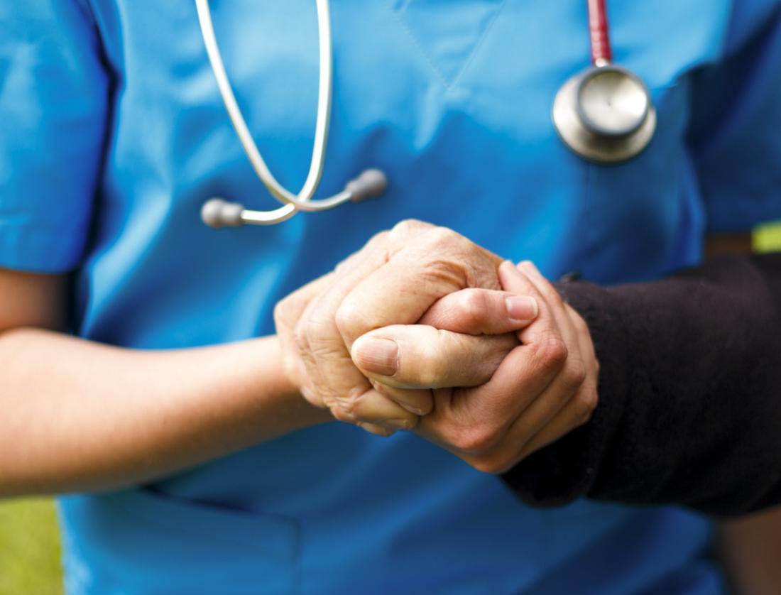 Doktor, der die Hand des Patienten hält