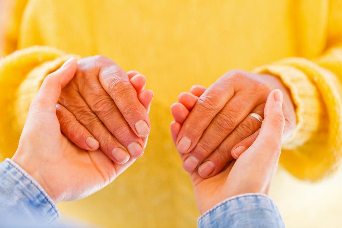 personne âgée atteinte de la maladie de Parkinson ayant les mains en l'air.