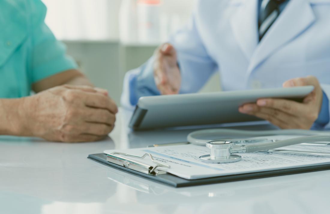 Médecin discutant des résultats avec le patient, avec un presse-papiers et un stéthoscope au premier plan.