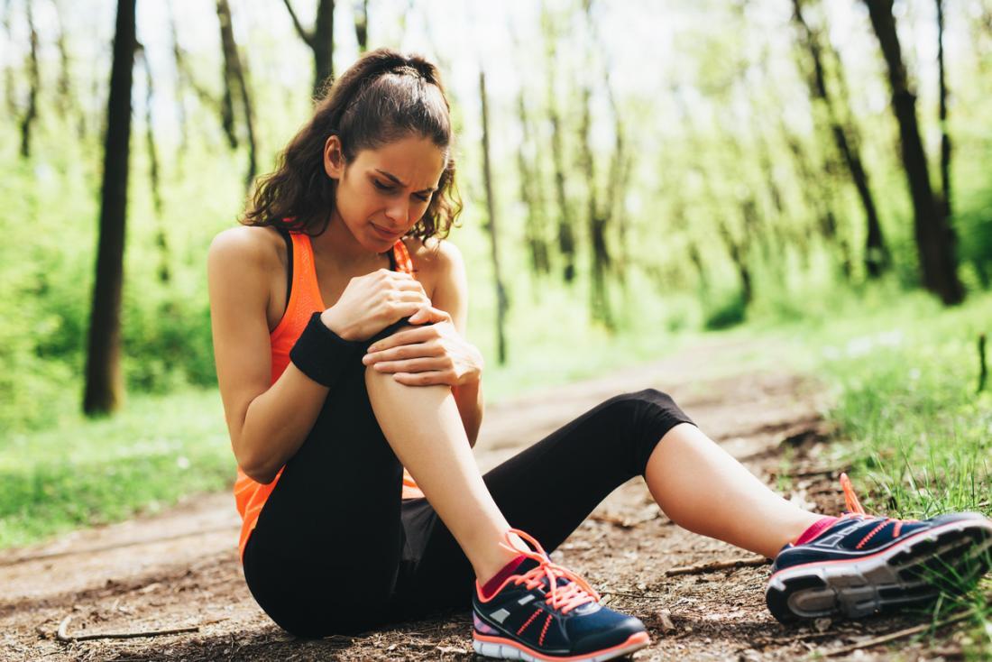 Żeński jogger obsiadanie na zmielonym mienia kolanie