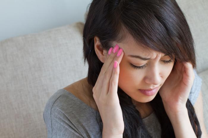 Жена с главоболие се вкопчва в главата си.