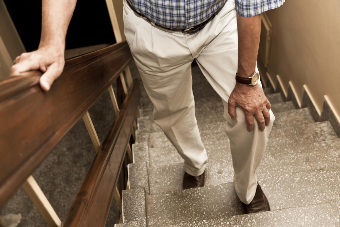 Homem segurando a parte superior da sua coxa enquanto subindo as escadas.
