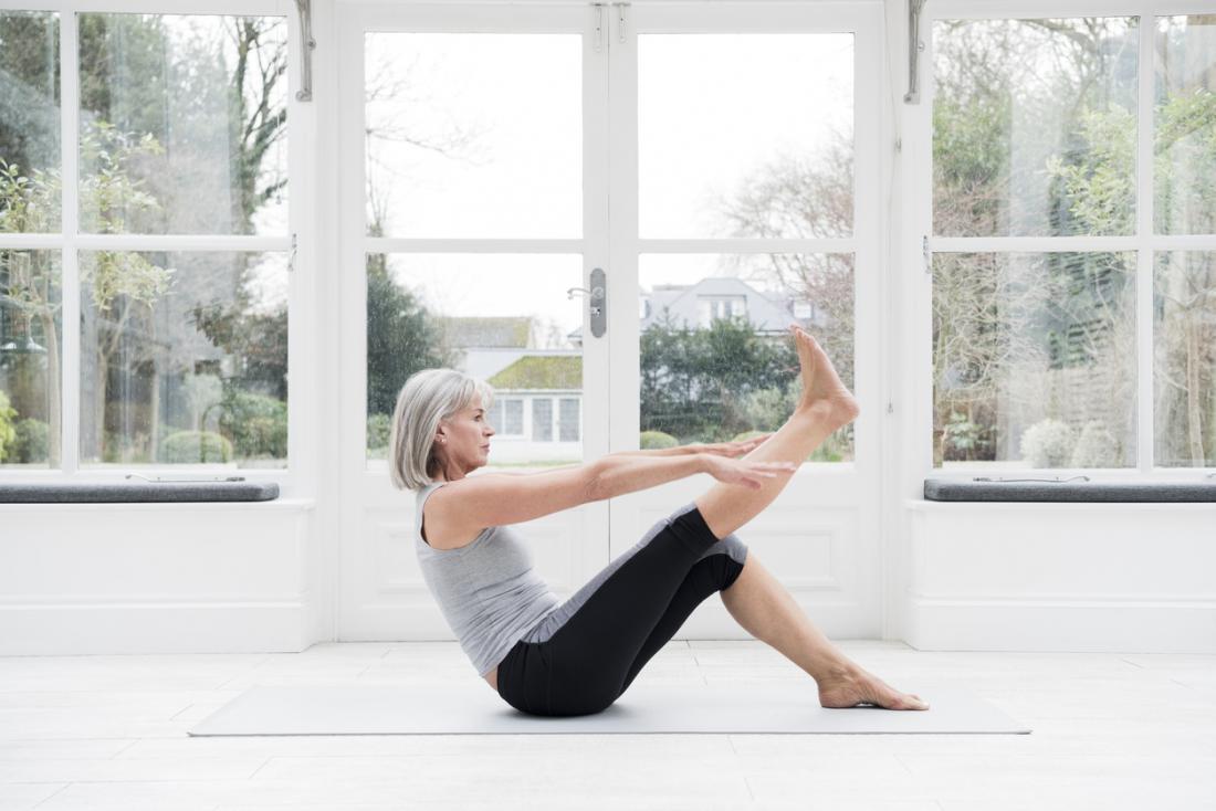 Mulher adulta mais velha, esticando as pernas durante os exercícios em casa