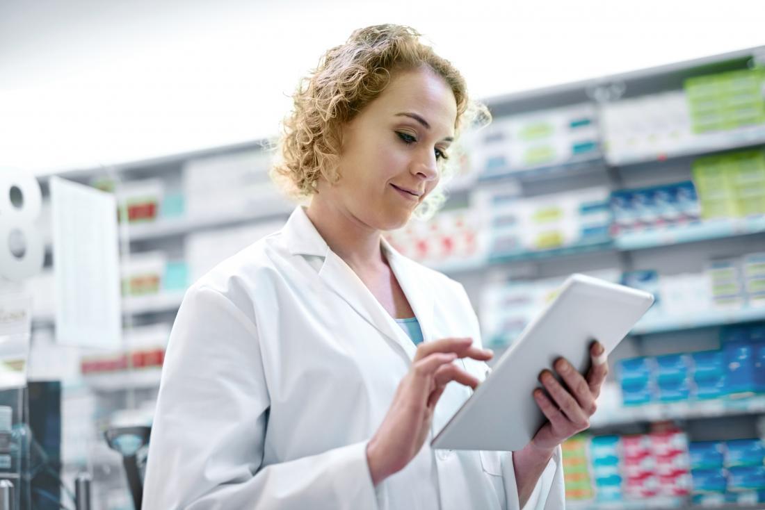 Pharmacien femelle regardant la tablette devant les étagères.