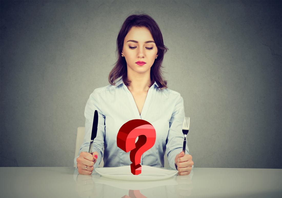 một người phụ nữ nhìn vào một cái đĩa với một dấu hỏi trên đó