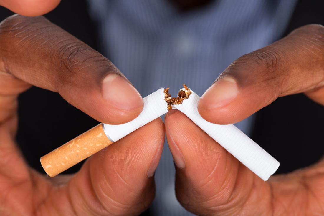 Bàn tay của người đàn ông chụp một nửa thuốc lá