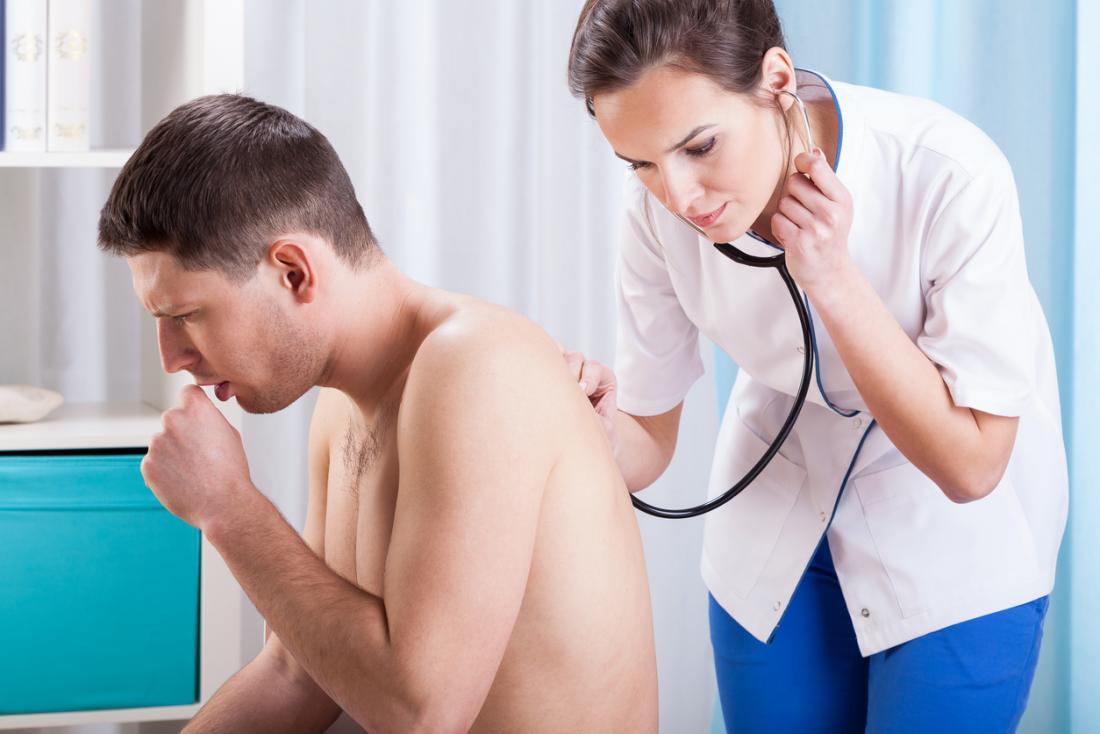 Bệnh nhân nam mặc áo sơ mi ho trong khi bác sĩ nữ lắng nghe hơi thở của anh bằng ống nghe trên lưng.