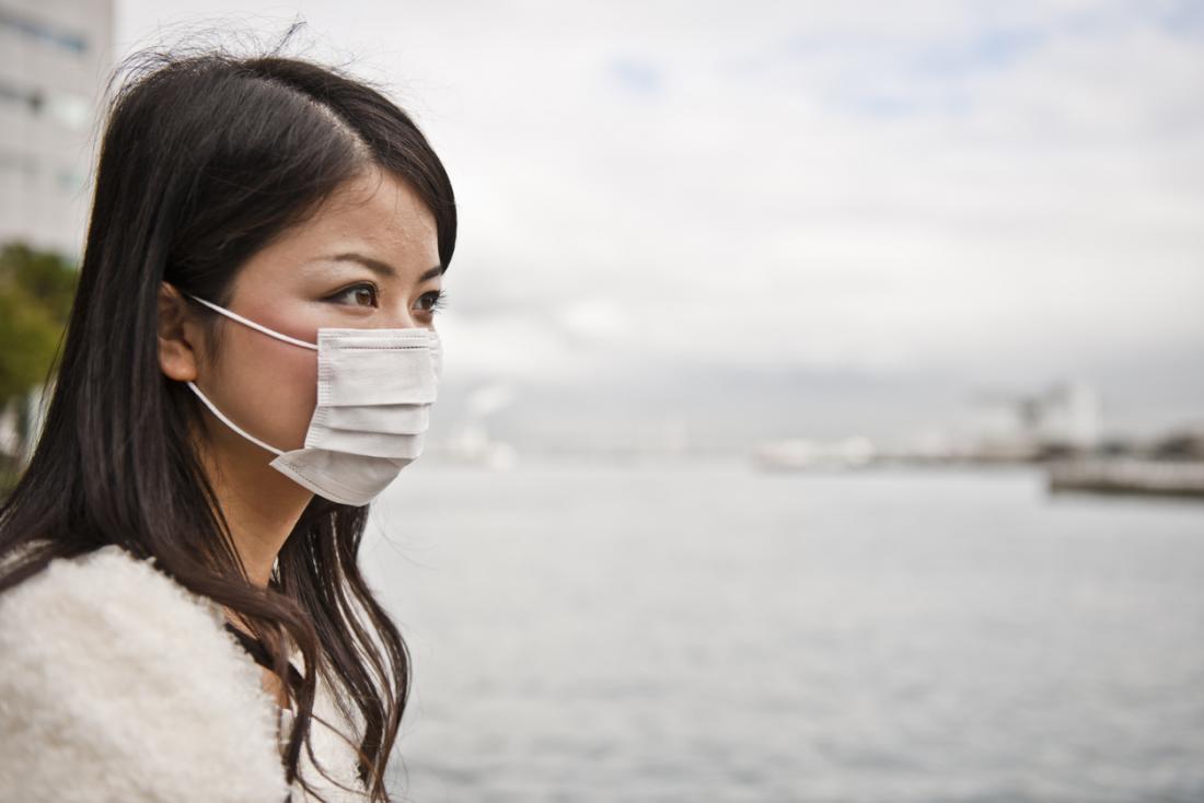 Femme portant un masque de pollution sur sa bouche sur le front de mer.