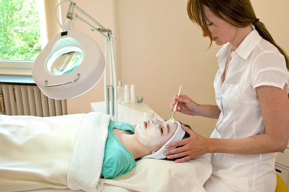 美容クリニックで化学的な顔の皮を受けている女性。