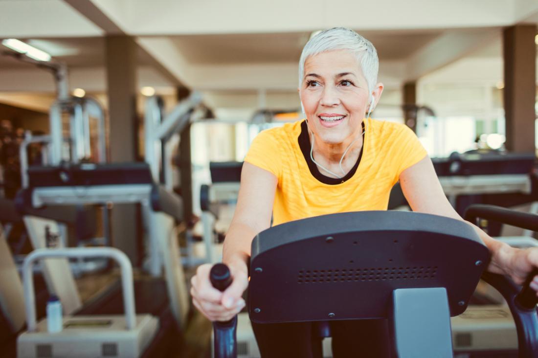 Người phụ nữ trưởng thành trên chiếc xe đạp tập thể dục trong phòng tập thể dục.