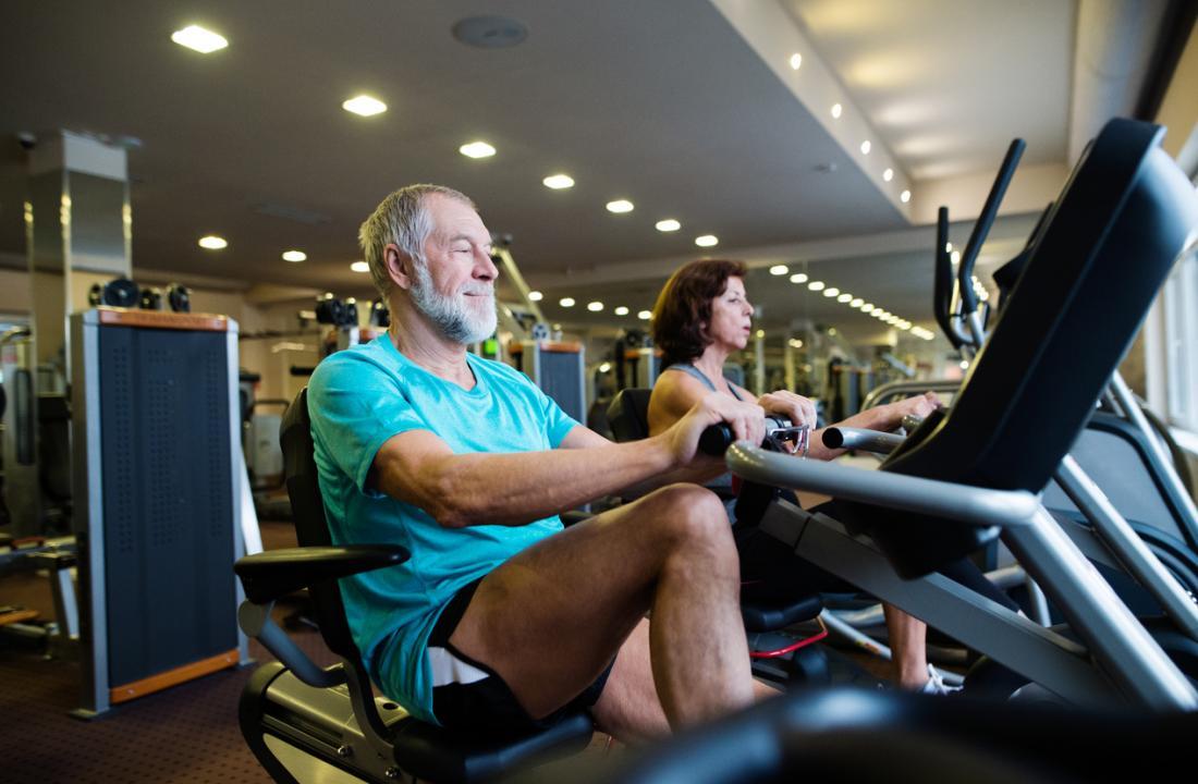 uomo anziano sulla cyclette reclinata in palestra.