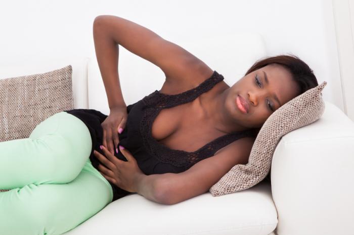 女性は胃の痛みで彼女の側に横たわっています。