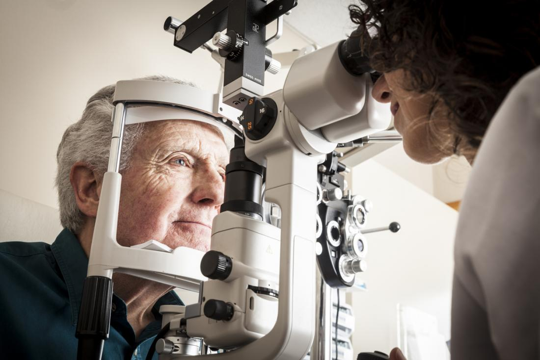 眼科医で眼科検査を受けている成人男性患者。