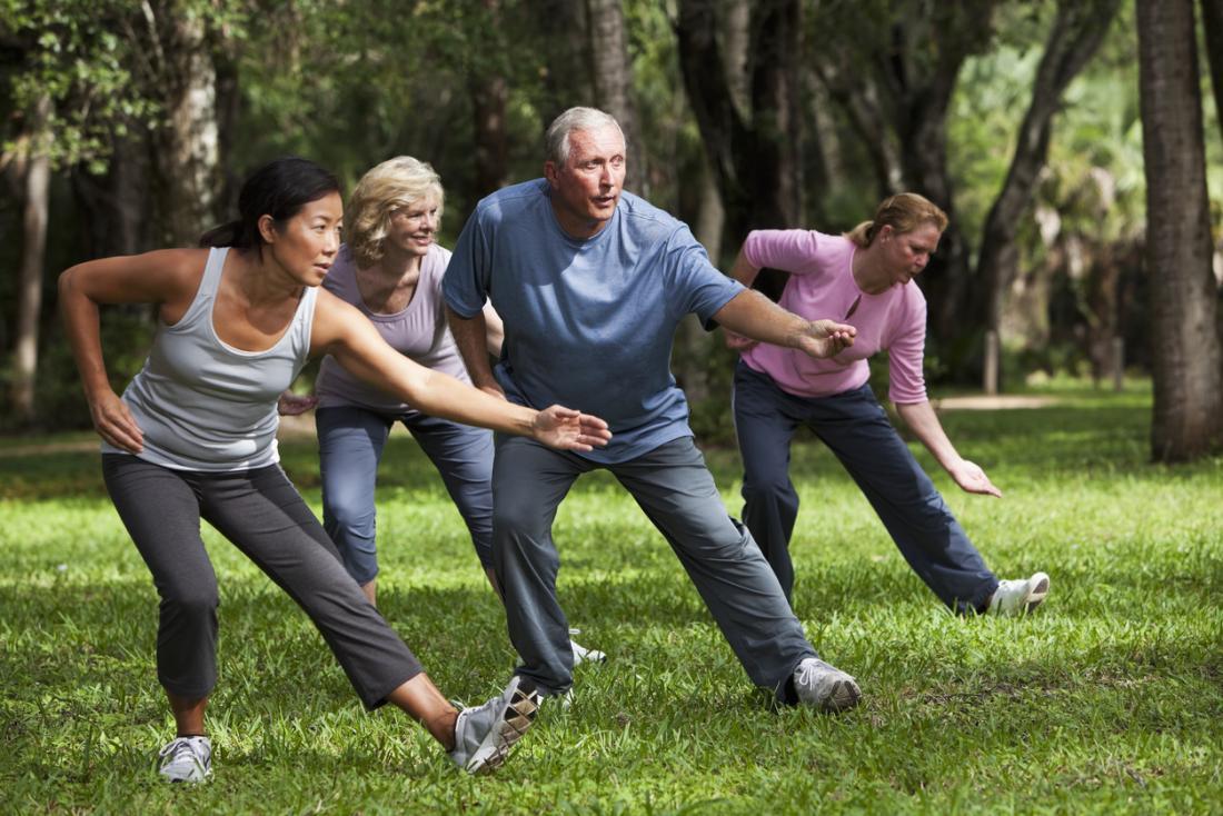 Grupa praktykująca tai chi i uważność w parku.