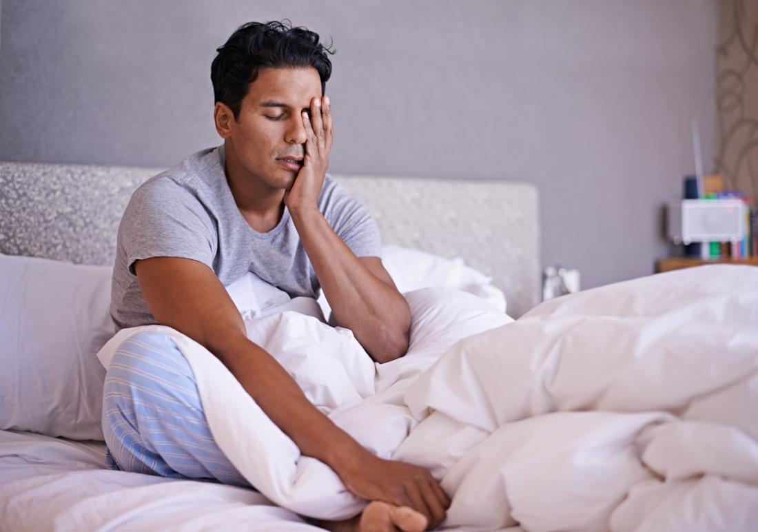 homme fatigué au lit