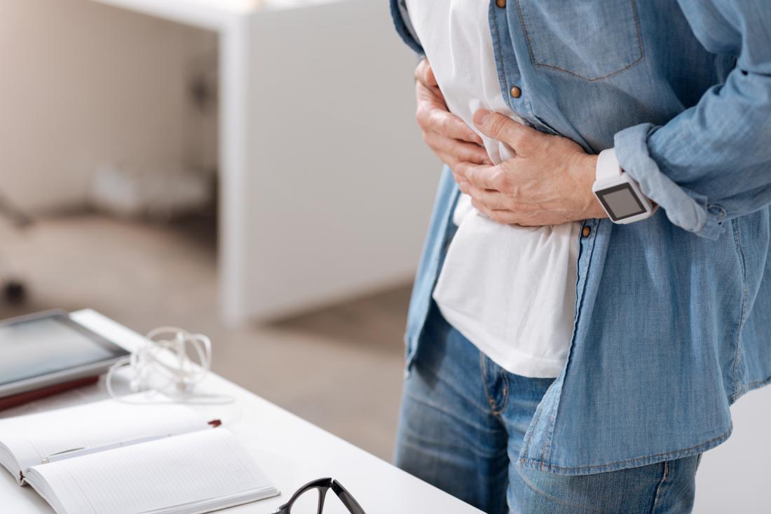 uomo che tiene il suo stomaco nel dolore a causa della colite ulcerosa e della stitichezza
