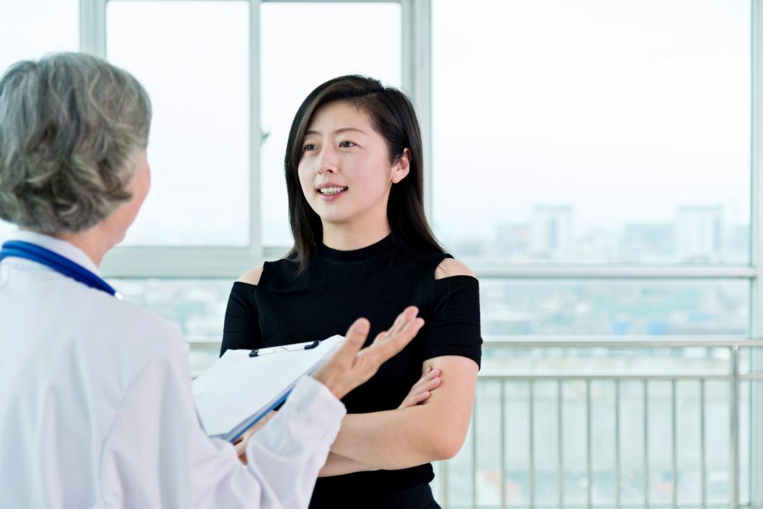 Paziente femminile che sta e che parla con medico femminile