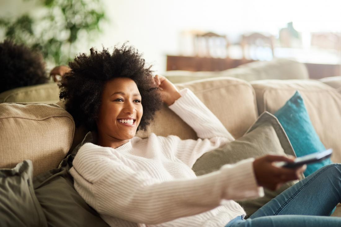 Bequeme Frau, die auf der Couch fernsieht sich entspannt