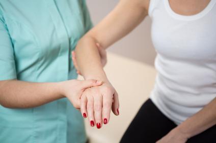 медицинска сестра, която прави физиотерапия на ръката на дамата