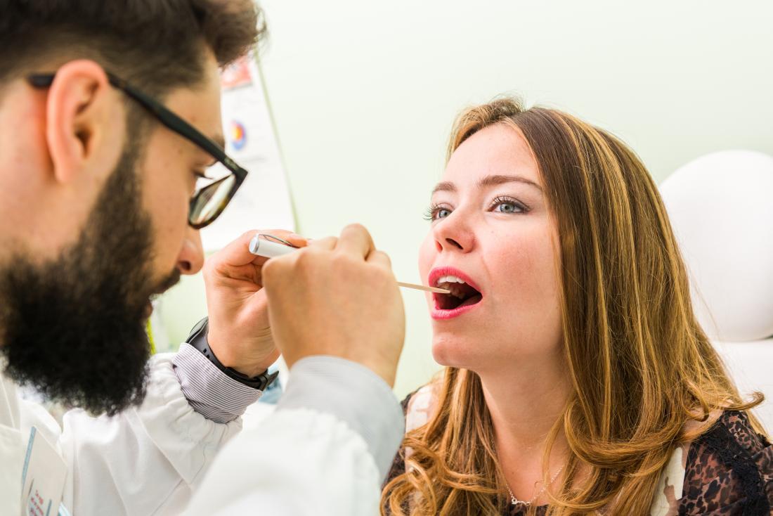 Người phụ nữ với lưỡi xanh được kiểm tra bởi nha sĩ hoặc bác sĩ.