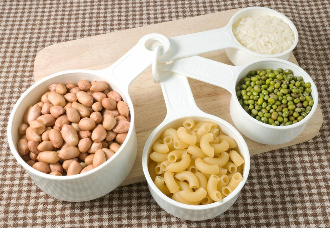 Cuillères à mesurer avec des pâtes séchées, des haricots et des légumineuses.