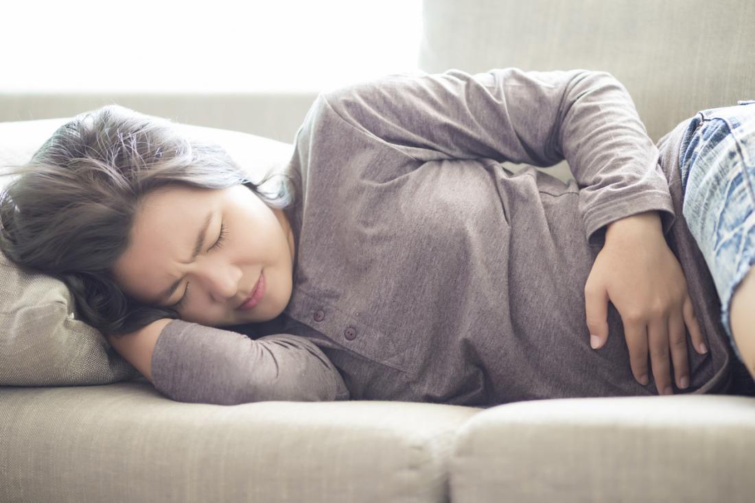 Femme allongée sur le côté sur un canapé, tenant son estomac dans la douleur, éprouvant des crampes d'époque et des ballonnements.