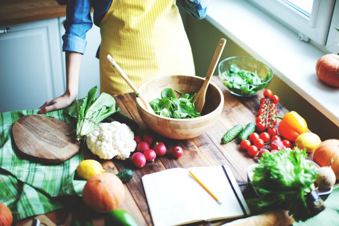 Femme faisant une salade dans la cuisine sur la table en bois avec livre de recettes. Les ingrédients comprennent le poivre, les tomates, les radis, les épinards, le chou-fleur et d'autres légumes.