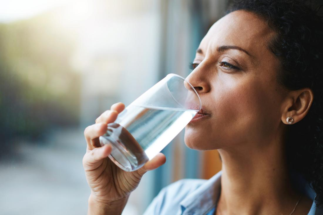 Femme buvant de l'eau à partir d'un verre, rester hydraté.