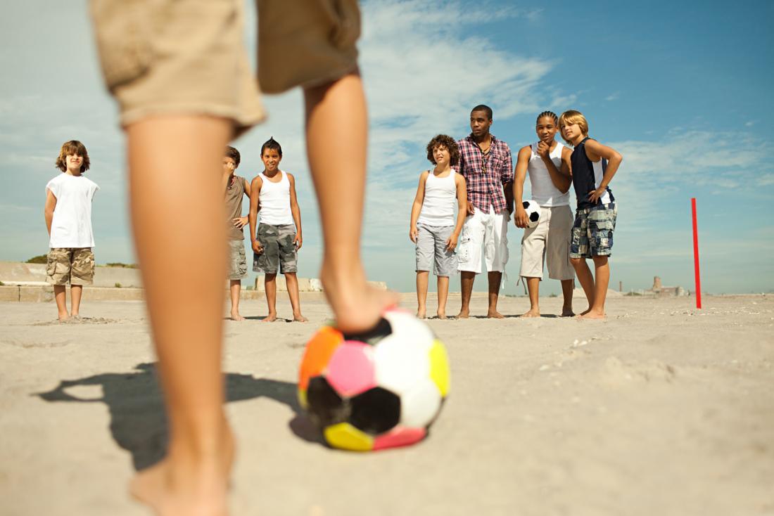 garçons jouant au football de plage