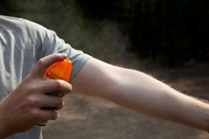 Insektenschutzmittel wird auf einen Arm gesprüht.