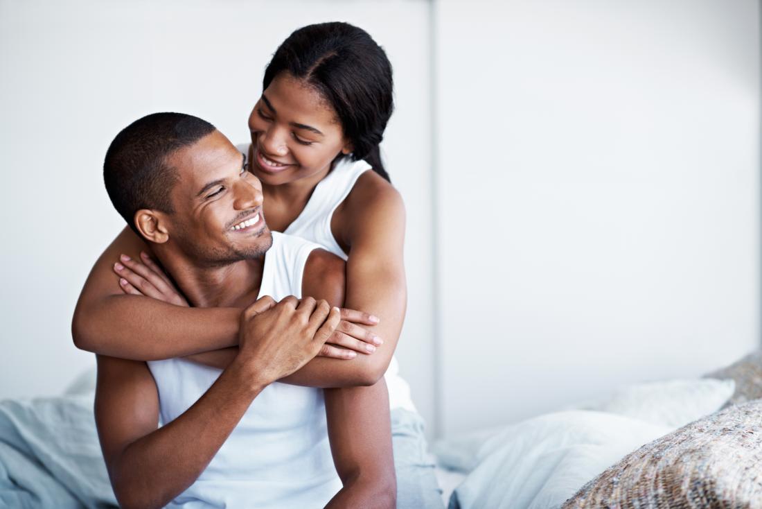 млада черна двойка, прегръщаща се на леглото