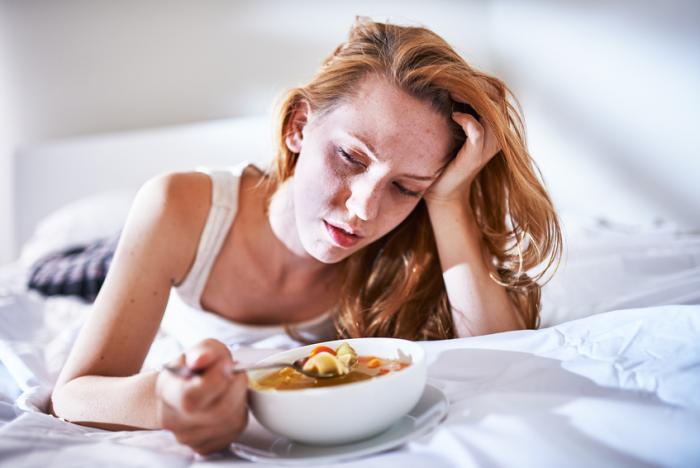 [Eine kranke Frau im Bett isst Suppe]