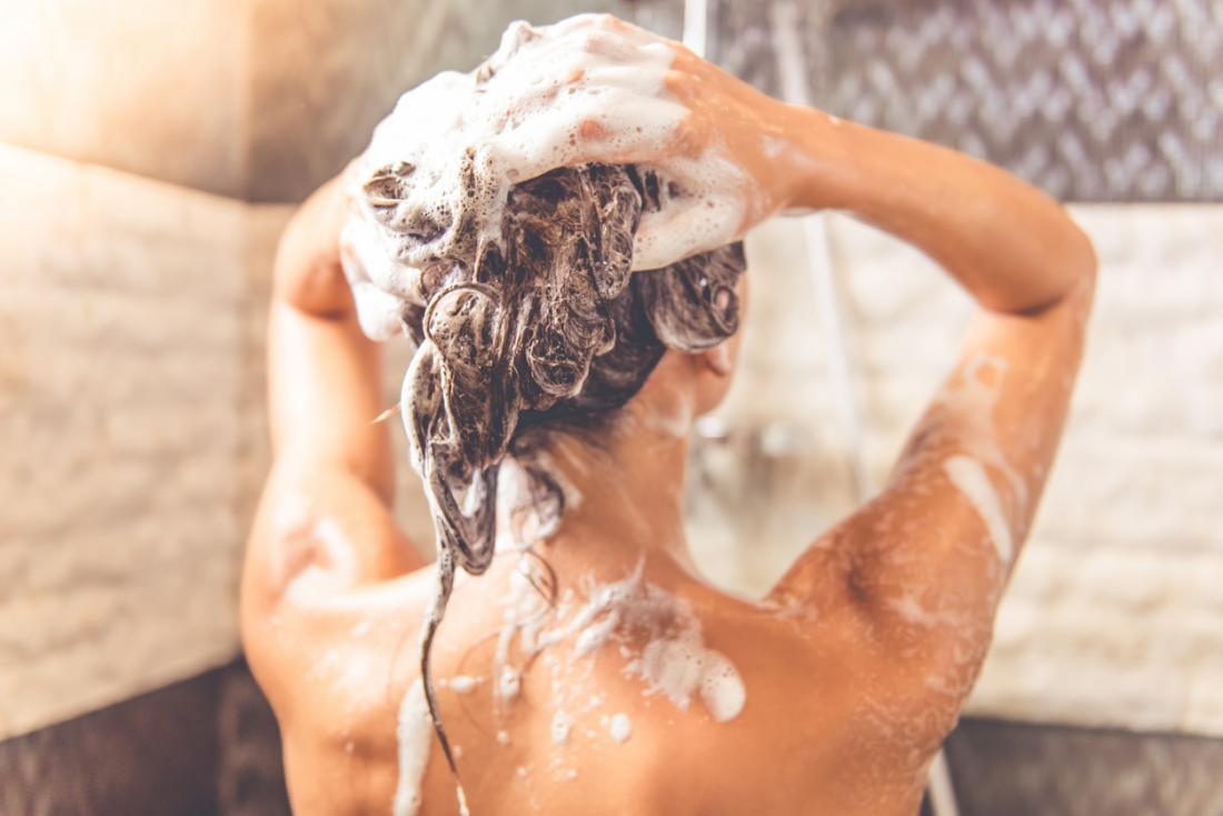 Dame dans une douche lavant ses cheveux