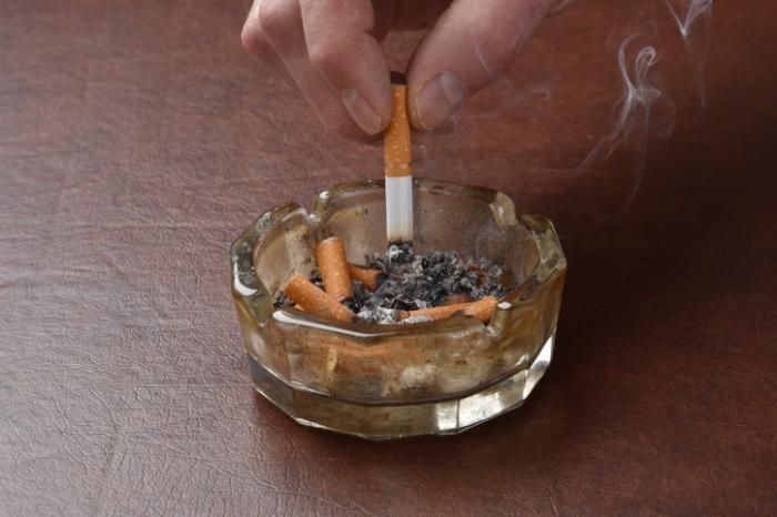灰皿に紙巻きタバコを入れる