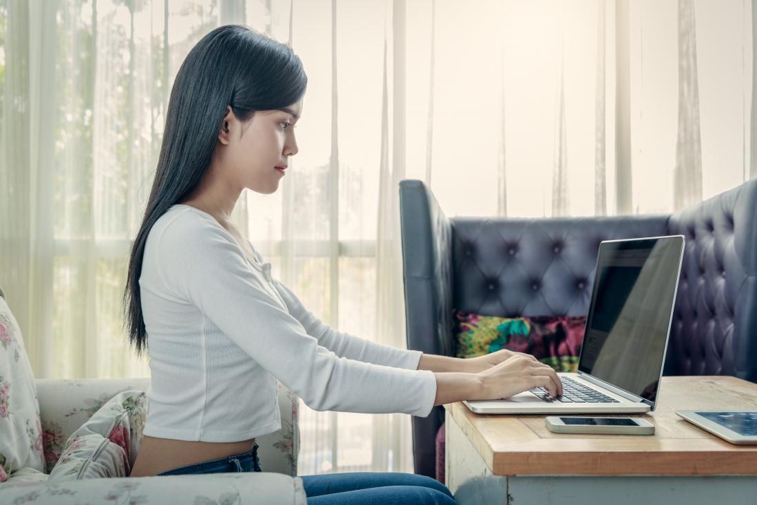 女性がノートパソコンでストレートタイピングをしていると、良い姿勢のための座位。