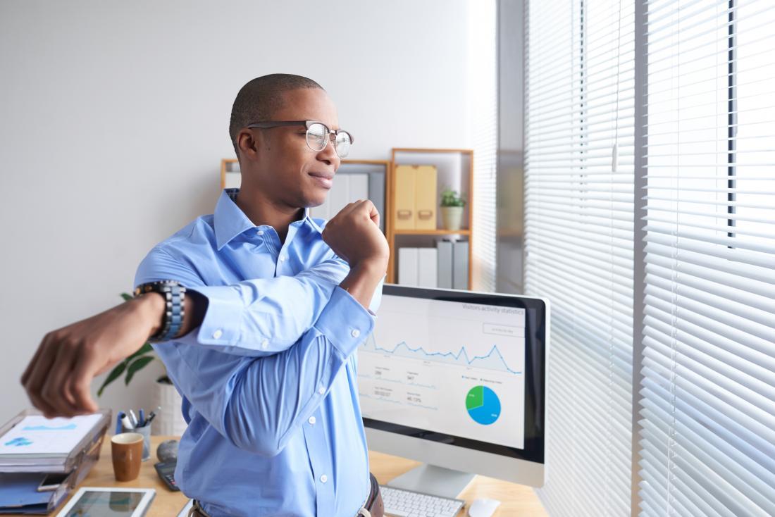 彼の腕と肩を伸ばしてオフィスに立っている男。