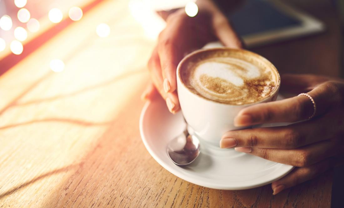 uma mulher tomando uma xícara de café