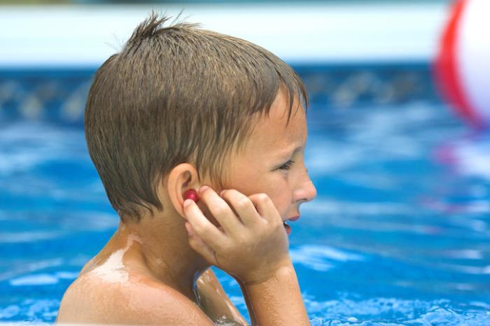 yüzme havuzunda kulak tıkacı koyarak çocuk