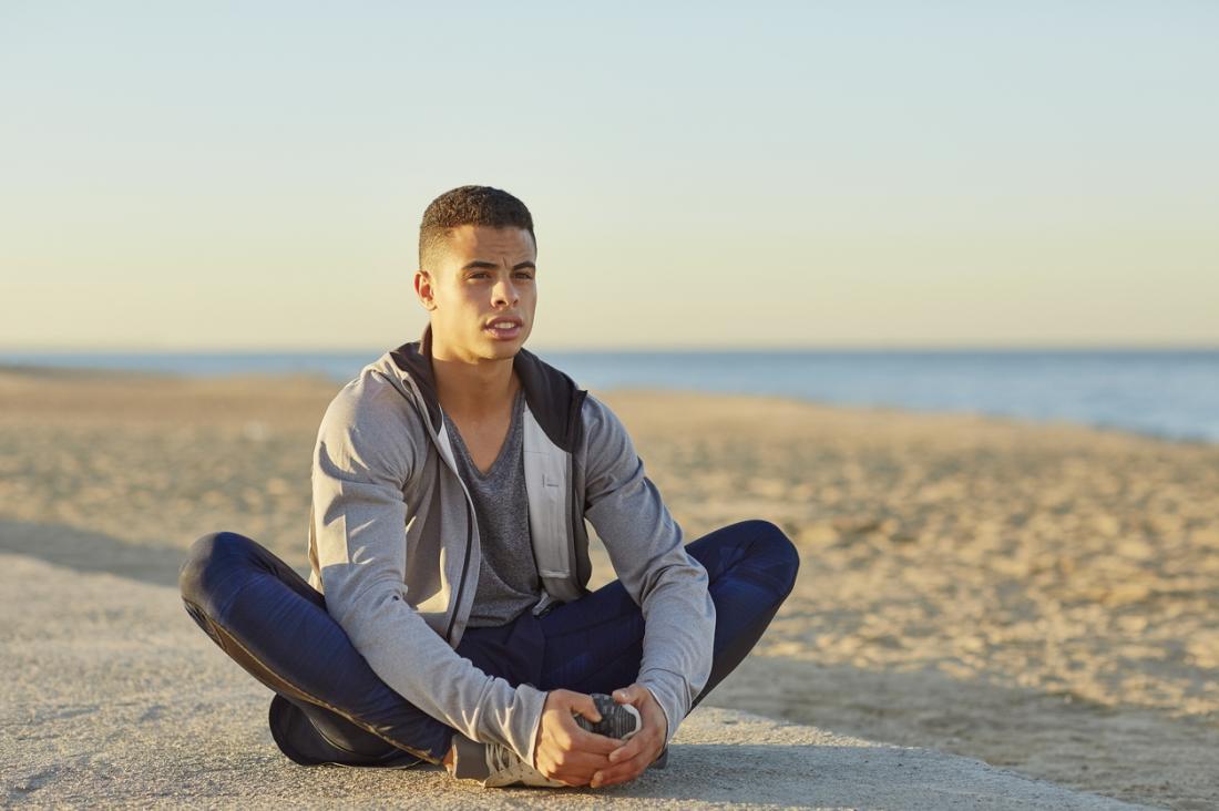Jovem fazendo ioga na praia em pose de sapateiro, ou Baddha Konasana.