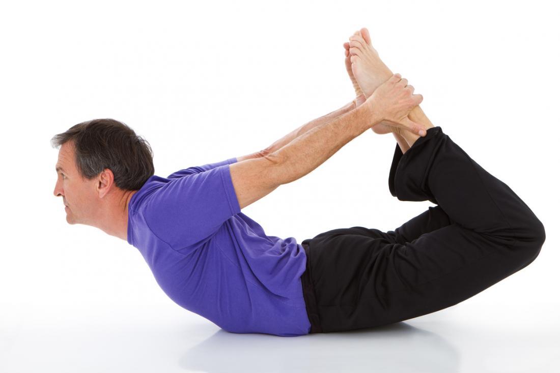 Homem que faz a ioga na pose da curva, ou dhanurasana.