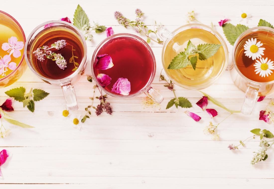 Fünf Tassen Kräutertee in einer Reihe, einschließlich Hagebutte, Nessel und Löwenzahn Tee.