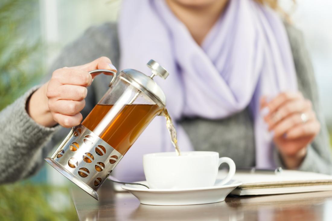 Strömender Tee der Frau in eine Schale.