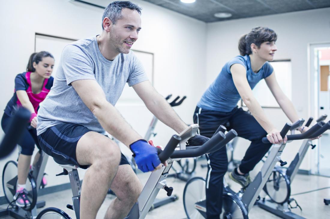 Spinning-Klasse in der Turnhalle, mit drei Personen, die auf Fahrrädern trainieren.