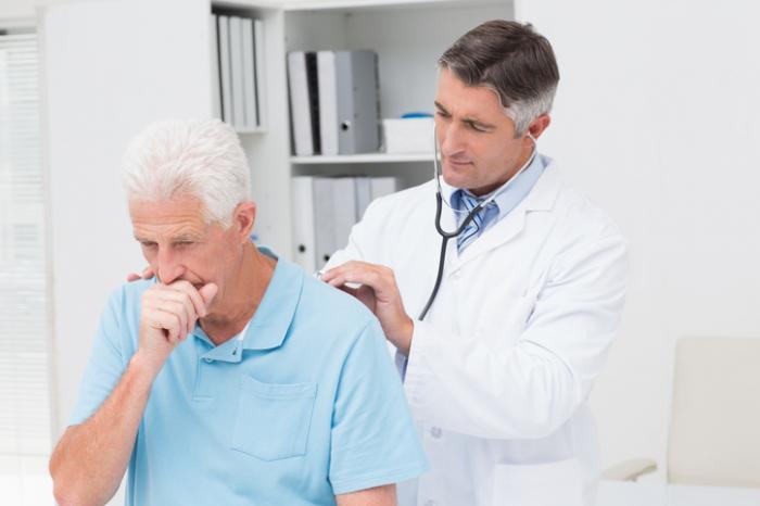 [il dottore controlla un paziente maschio anziano che sta tossendo]