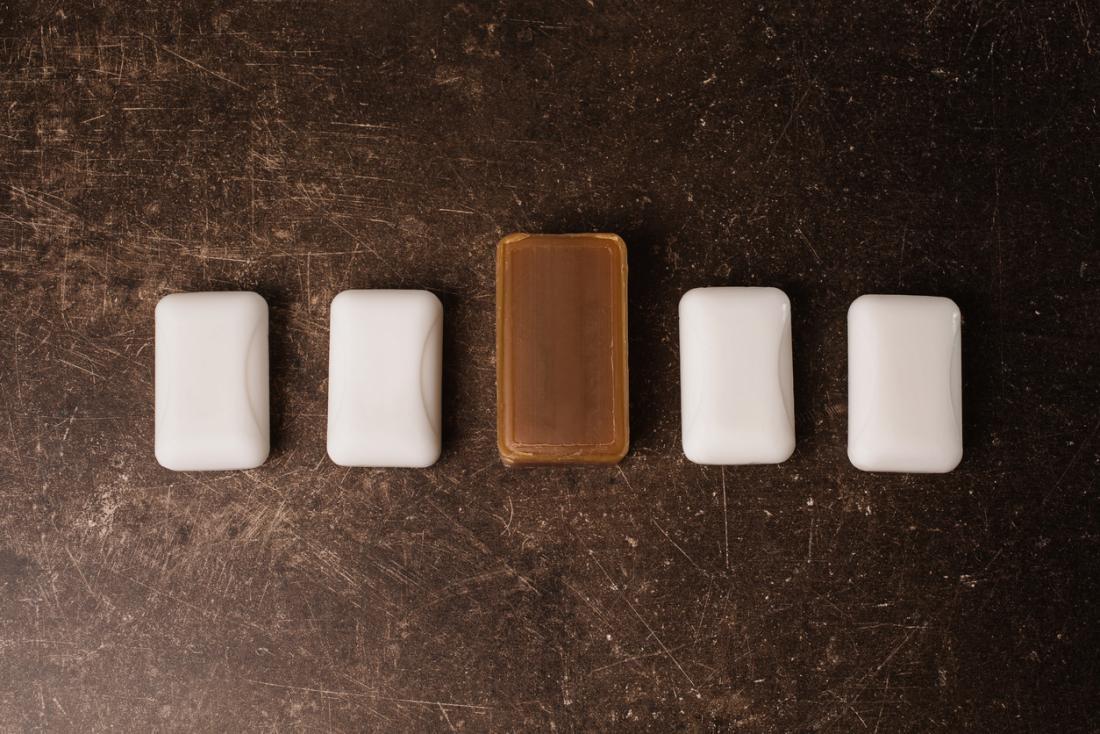 Quattro barre di sapone bianco disposte, con una barra più grande di sapone di catrame nel mezzo.