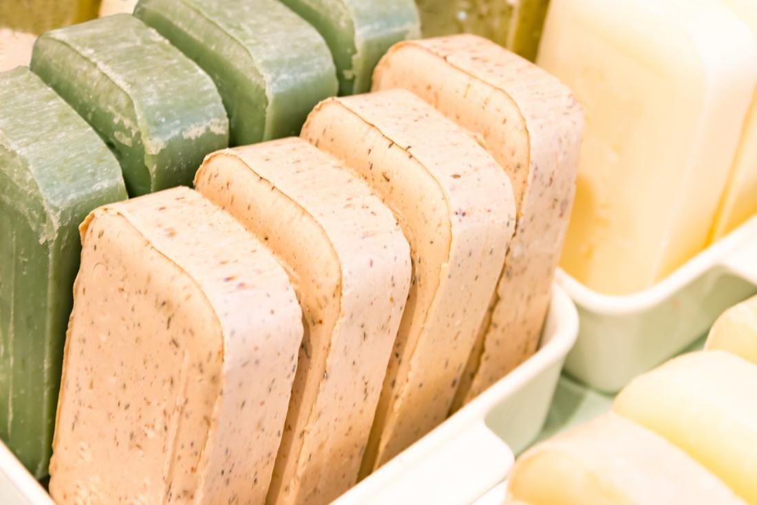 Barre di sapone naturali di diverso colore allineate nei piatti, una con pezzetti esfolianti.