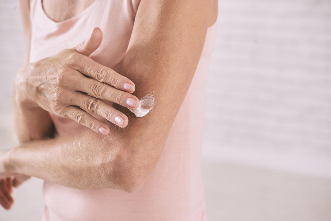 donna matura che applica la lozione per la pelle al suo braccio.