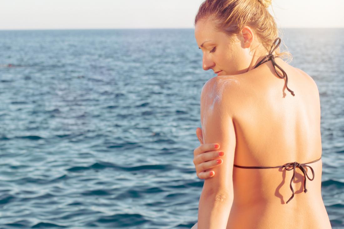 Жена в бикини на плажа, поставяйки suncream върху кожата.